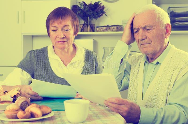 Starzejąca się para ono zmaga się wynagrodzenie rachunki fotografia royalty free