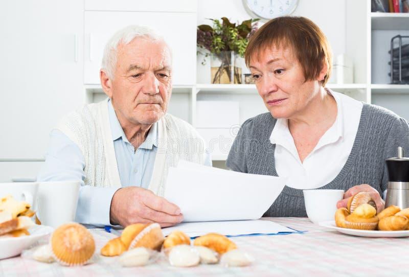 Starzejąca się para ono zmaga się wynagrodzenie rachunki zdjęcia royalty free