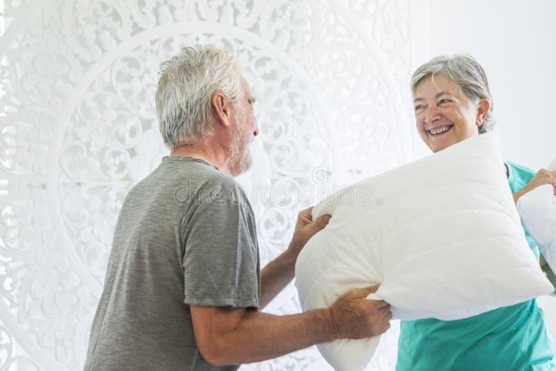 Starzej?ca si? starsza doros?a caucasian para zabaw? robi wojnie z poduszkami w domu przy rankiem w sypialni - bia?y jaskrawy pok obraz royalty free