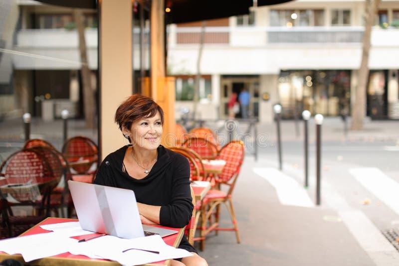 starzejący się żeński pisarz pracuje z nową książką w laptopie i zdjęcia royalty free