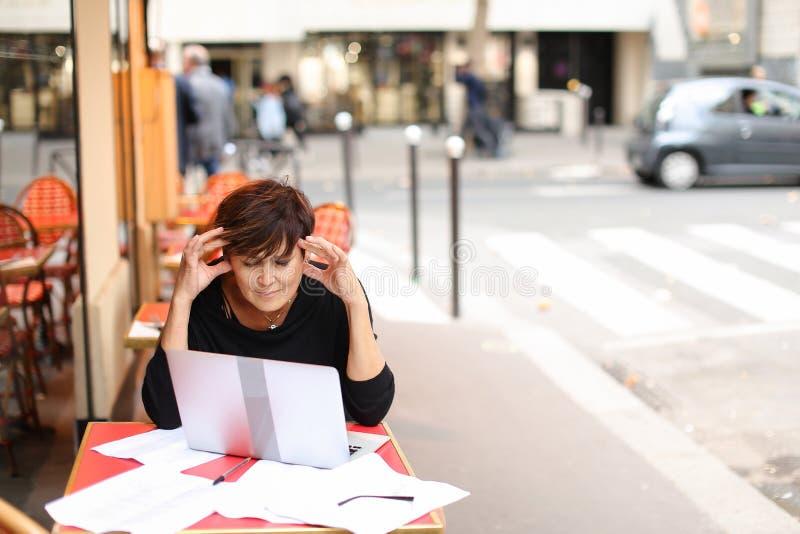 starzejący się żeński scenarzysta pracuje z scenariuszem w laptopie zdjęcie royalty free