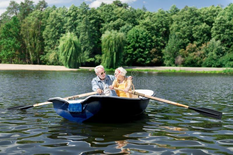 Starzejący się żony i męża mienia paddles ma ładną rzeczną wycieczkę w łodzi zdjęcia royalty free