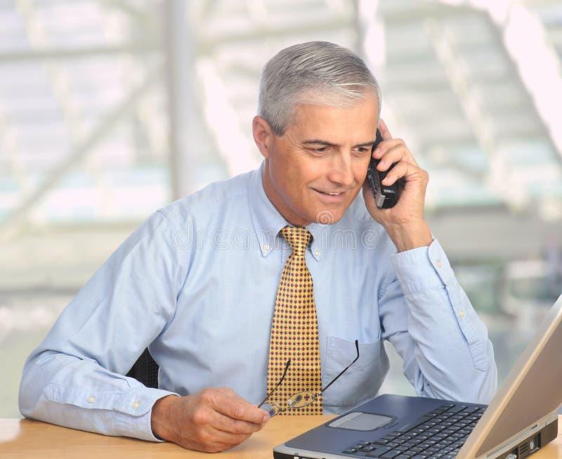 starzejący się biznesmena laptopu środkowy telefon obraz stock