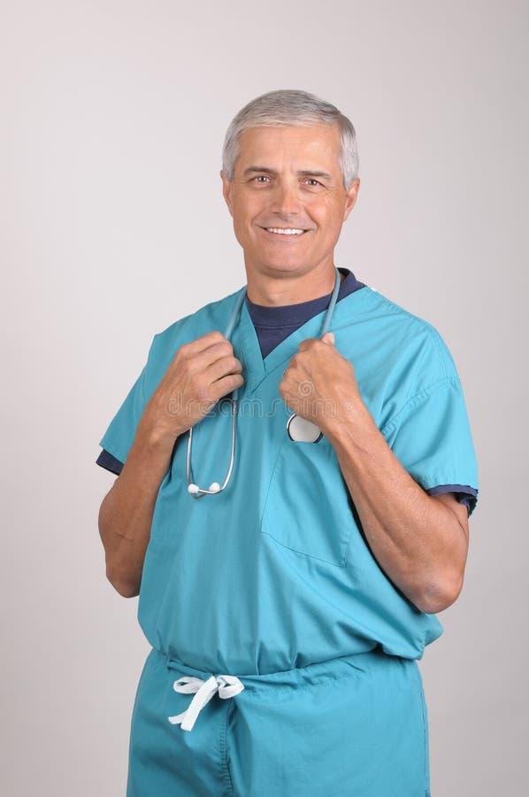starzejący się doktorski środek szoruje stetoskop zdjęcia stock