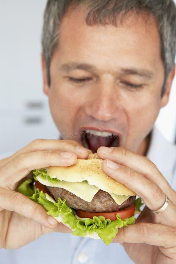 starzejący się hamburgeru łasowania mężczyzna środek obrazy royalty free