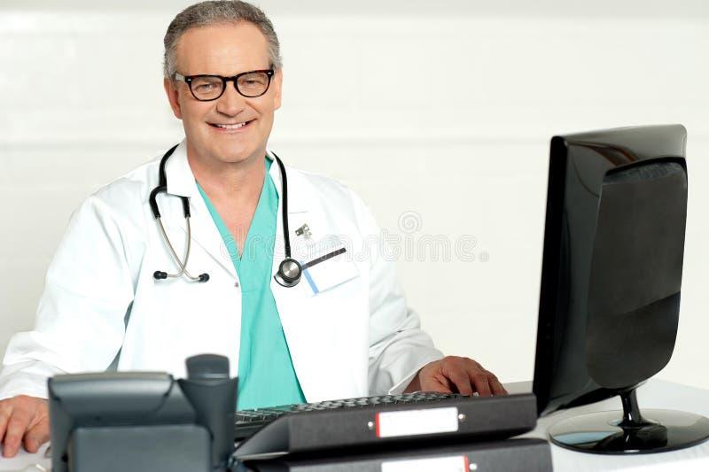 Starzejący się lekarz z stetoskopem wokoło jego szyi obrazy royalty free