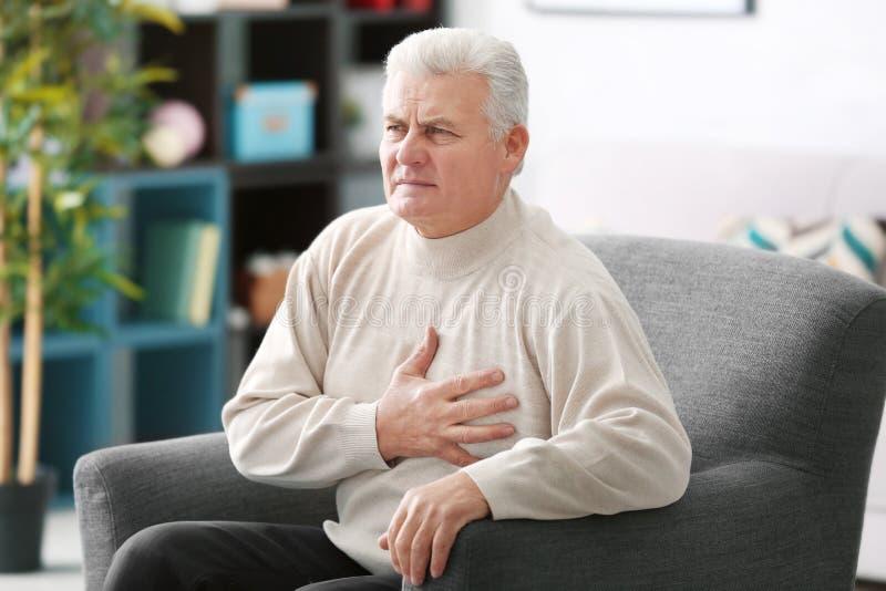 Starzejący się mężczyzna ma serce ból fotografia stock