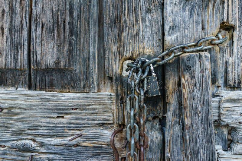 Starzejący się ośniedziały łańcuch z kędziorka ochraniaczem na starym antycznym drewnianym drzwi obrazy royalty free