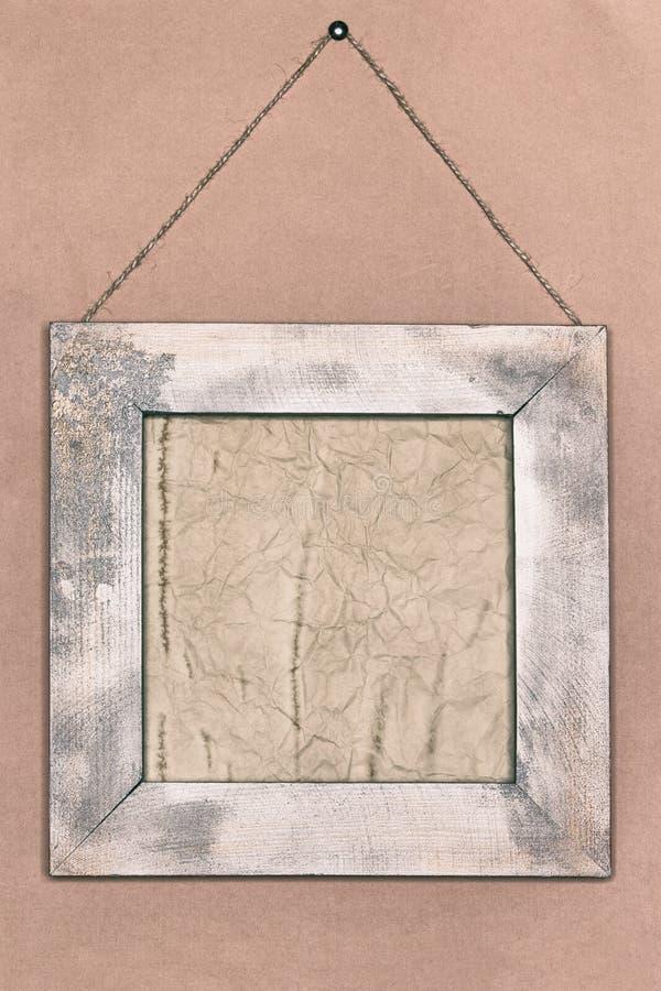 Starzejący się papier w podławej drewnianej ramie na starej tapety ścianie zdjęcia stock