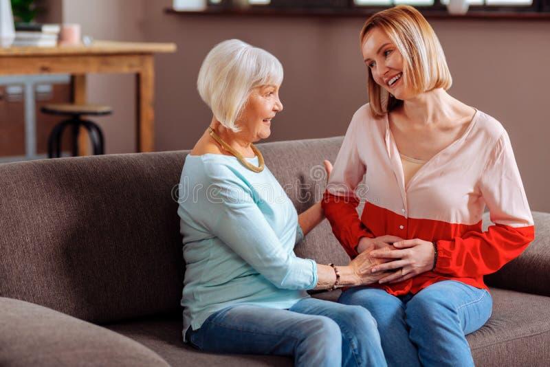 Starzejący się szczęśliwego promieniejącego madam czule palming jej córki dziecka wpadać na siebie obraz stock