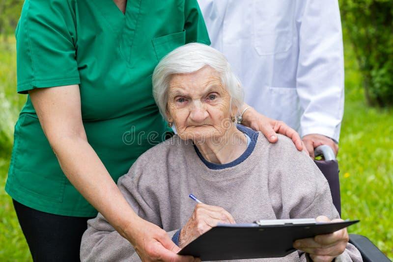 Starzej?ca si? kobieta w w?zku inwalidzkim z medyczn? pomoc? zdjęcie royalty free