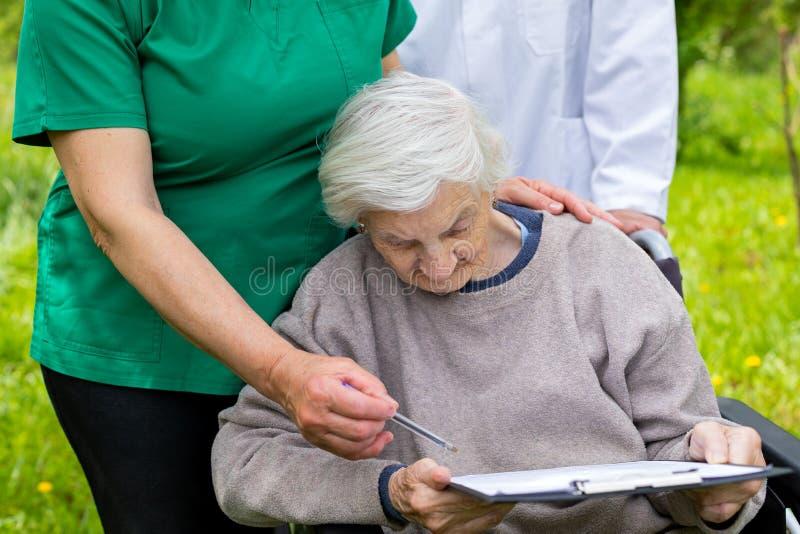 Starzej?ca si? kobieta w w?zku inwalidzkim z medyczn? pomoc? zdjęcia royalty free