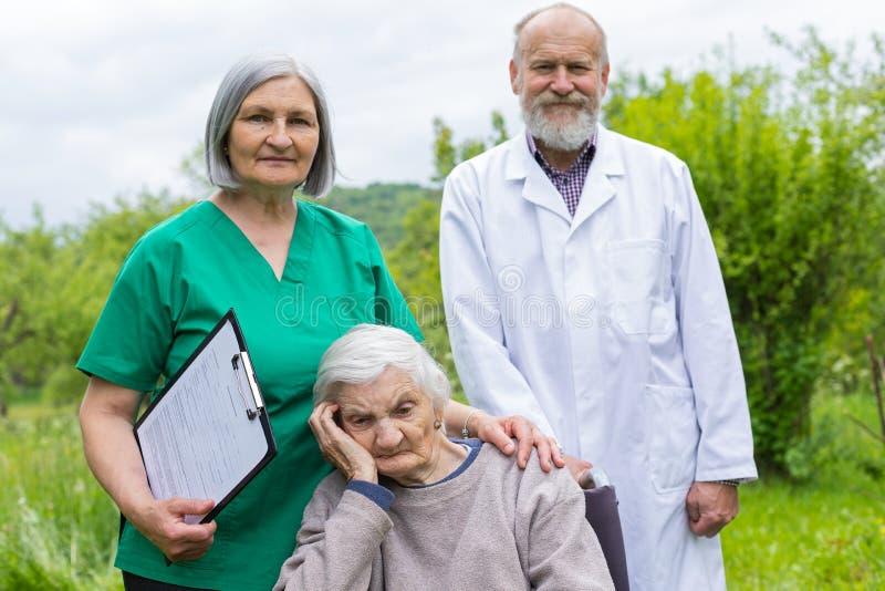 Starzej?ca si? kobieta w w?zku inwalidzkim z medyczn? pomoc? fotografia stock
