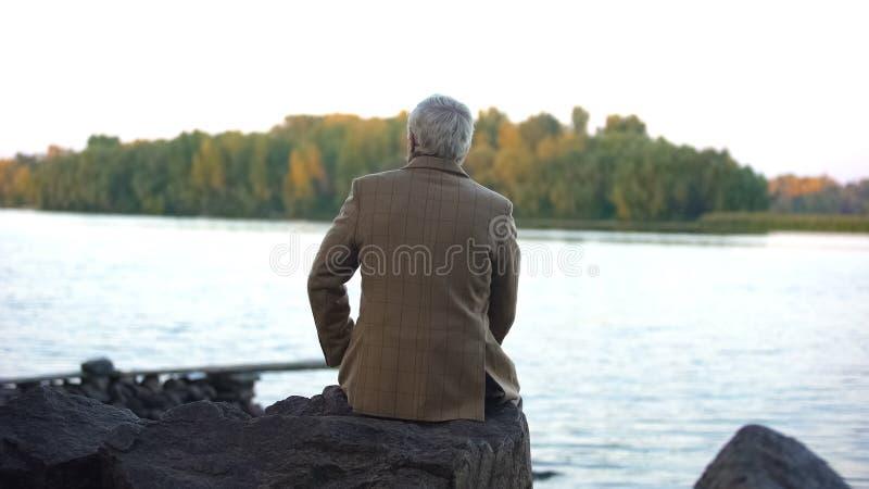 Starzej?cy si? m?ski obsiadanie na kamiennym brzeg rzekim, my?le? ?ycie, cieszy si? natura widok obraz royalty free