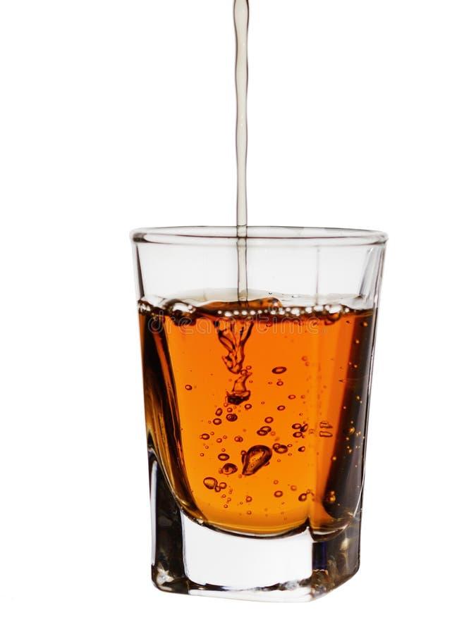 Starzeje się w baryłce dla kilka rok, alkohol nalewa w małą szklaną zlewkę, odizolowywającą na białym tle obraz stock