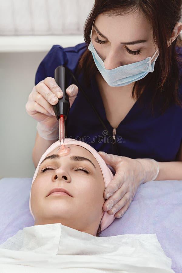 Starzenie się twarzowy Model otrzymywa fizjoterapię, procedura de Piękno salon, kosmetologia Model i lekarka, zakończenie fotografia royalty free