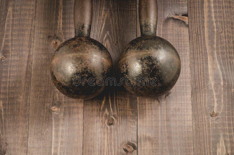 Starzy żelazni dumbbells/starzy żelazni dumbbells na ciemnym drewnianym tle Odgórny widok fotografia royalty free