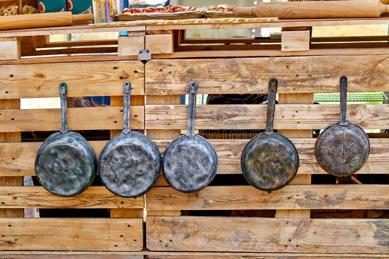 Starzy żelazo garnki, antyk smaży niecki i wieszają na haczykach kuchenni starzy naczynia zdjęcie stock