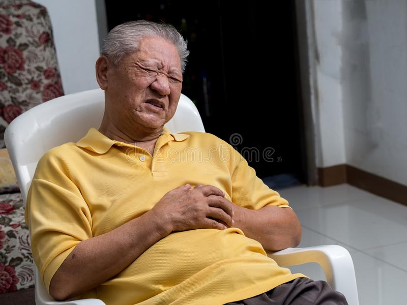 Starzy Azjatyccy mężczyzna siedzi na krześle przy żywym pokojem z atakami serca Oba starego człowieka ` s ręki na piersi przez ci fotografia stock