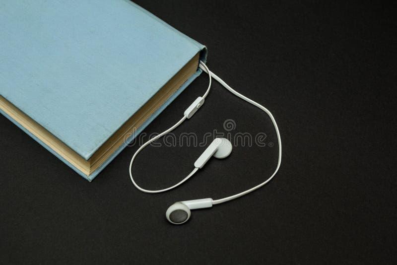 Starzy błękitni książki i białych hełmofony na czarnym tle, fotografia royalty free