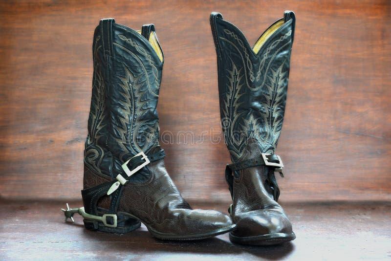 Starzy buty i ostroga nad drewnianym tłem zdjęcia royalty free