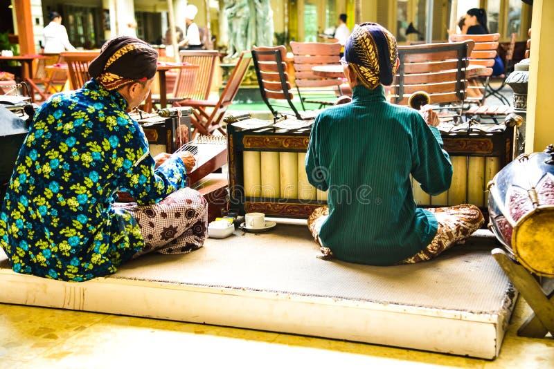 Starzy człowiecy jest ubranym tradycyjnego mundur bawić się z starymi i antycznymi muzycznymi instrumentami zdjęcia royalty free