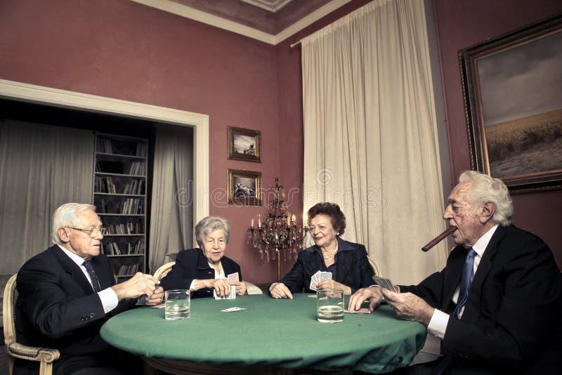 Starzy człowiecy i kobiety bawić się grzebaka zdjęcie royalty free