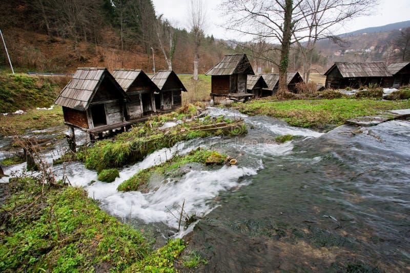 Starzy drewniani wodni młyny budowali na szybkim bieżącym rzecznym kanale w popularnej antycznej wiosce zdjęcie stock