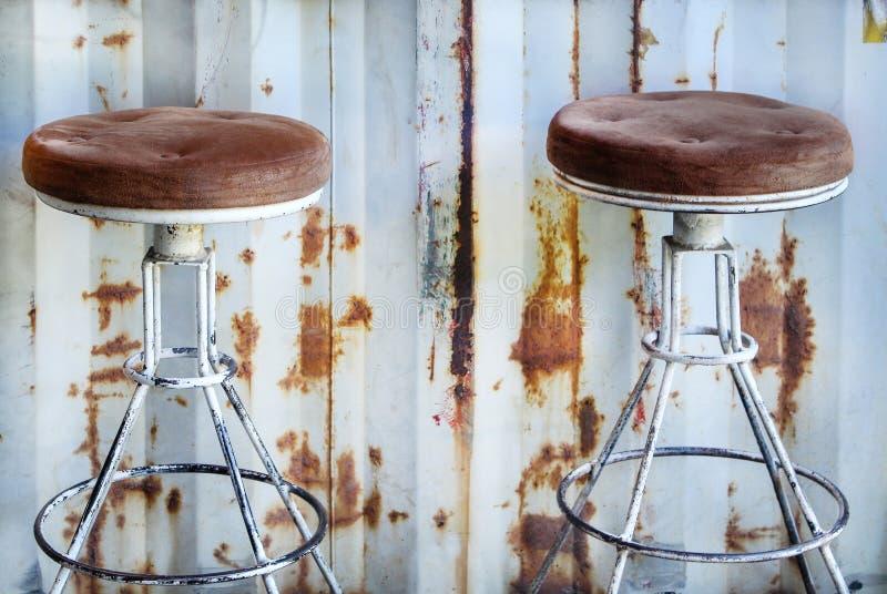 Starzy dwa stalowy krzesło na ośniedziałym cynk ściany tle obraz stock