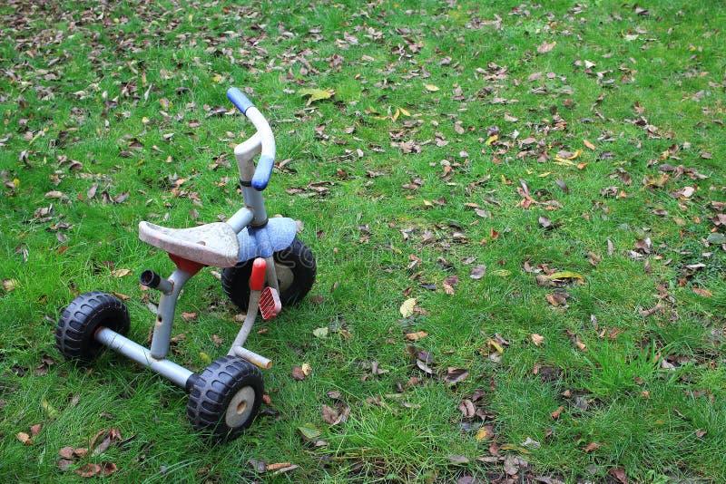 Starzy dziecko trójkołowa trzy koła jechać na rowerze w ogródzie obrazy royalty free