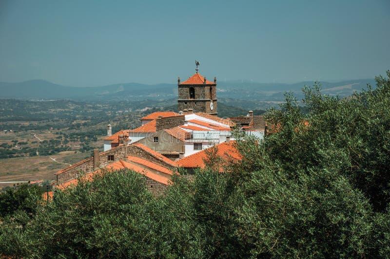 Starzy kamieni domy z ko?cielnym steeple i drzewem oliwnym w Monsanto obrazy royalty free