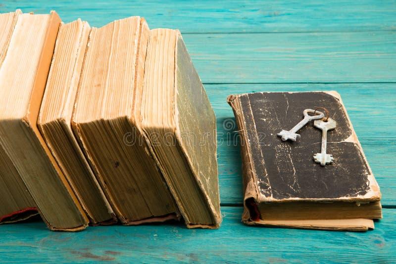 Starzy klucze na starej książce stercie antyk książki na błękitny drewnianym i fotografia stock