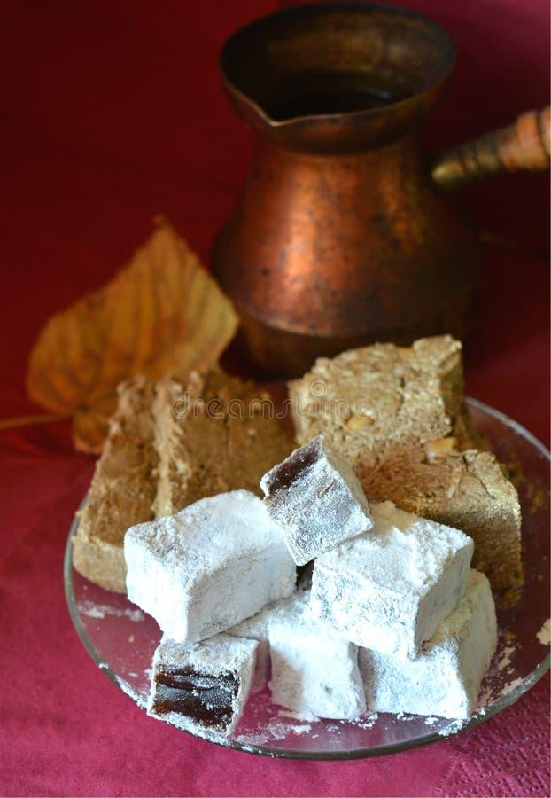 Starzy miedziani Tureckiej kawy garnki, Bliskowschodni cukierki i żółty liść na, Burgundy powierzchni i Burgundy tle zdjęcie royalty free