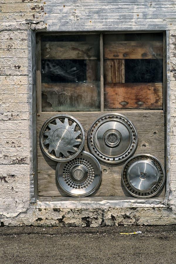 Starzy mieszani hubcaps w okno fotografia royalty free