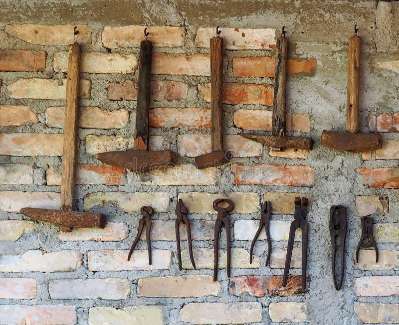 Starzy ośniedziali prac narzędzia wieszali na ściana z cegieł Rząd młoty różny rozmiar i rząd antyczni cążki underneath zdjęcie royalty free