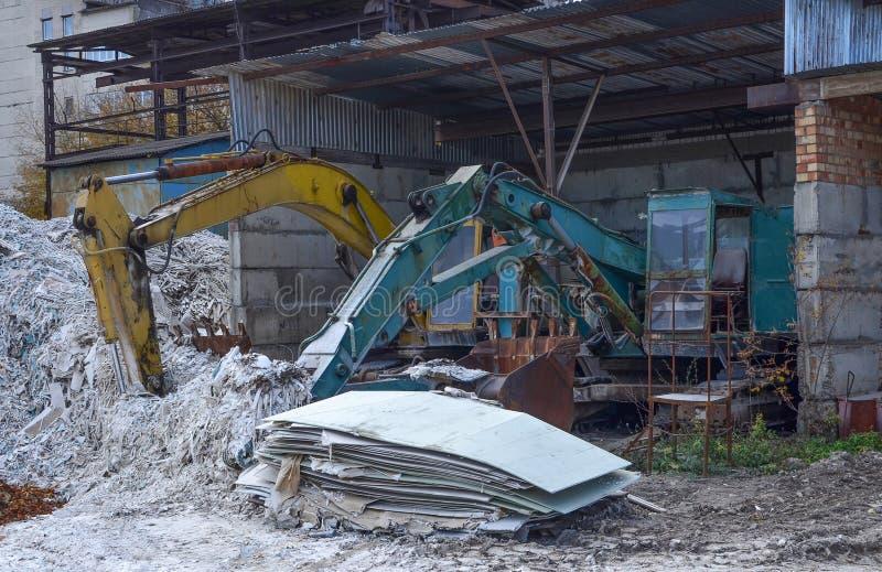 Starzy ośniedziali zaniechani budowa ekskawatory z wiadrem na ziemi w hangarze przy budową fotografia stock