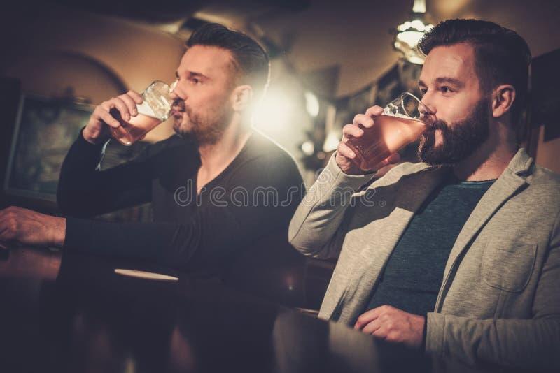 Starzy przyjaciele pije szkicu piwo przy barem odpierającym w pubie fotografia royalty free