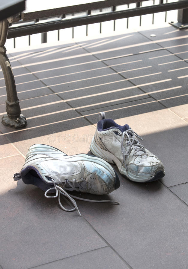 Starzy używać tenisowi buty kłaść na betonowej podłoga obrazy stock