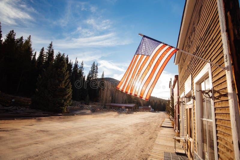 Starzy Zachodni Drewniani budynki z flagą zlani stany w St Elmo kopalni złotej miasto widmo w Kolorado, zdjęcie royalty free