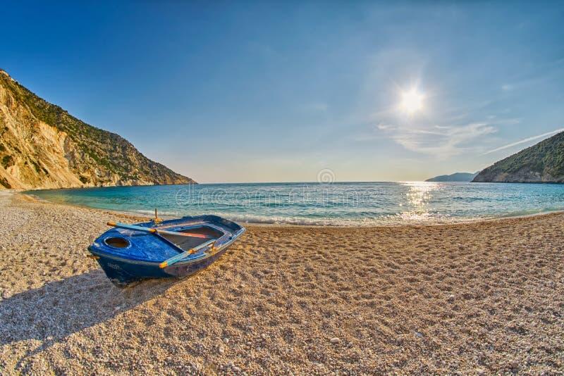 Starzy Zaniechani rybacy Łódkowaci przy zmierzchu Myrtos plażą w Kefalonia, Grecja zdjęcie stock