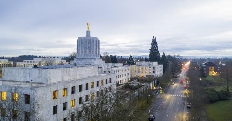 Morning Traffic Passes the Oregon Pioneer atop the Capital Building Salem. The state capital building adorned with the Oregon Pioneer with downtown Salem in the stock images
