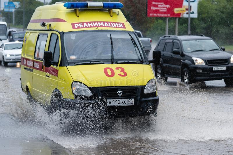 State Emergency Ambulance Reanimation Medical vehicle driving to help patient on city street road over deep muddy puddle, splashin. G water from wheels royalty free stock image