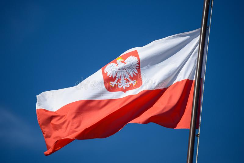 The state flag of Poland with the emblem of the Republic of Poland, on a background of blue sky, in the wind. stock images