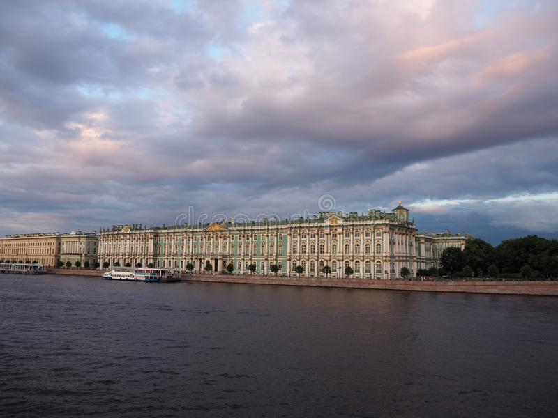The State Hermitage Museum in St. Petersburg, with a touristic boat in front of it, on the background of different color sky royalty free stock images