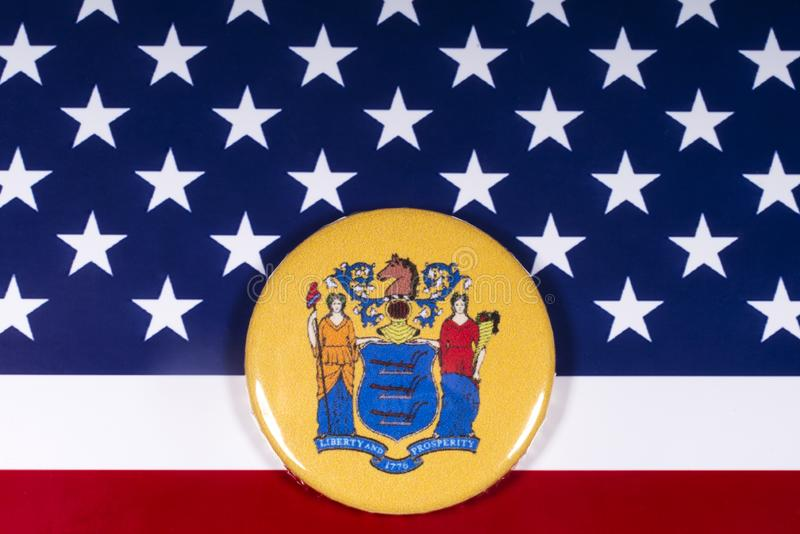 The State of New Jersey in the USA. London, UK - November 15th 2018: The coat of arms of the State of New Jersey, pictured over the flag of the United States of royalty free stock photo
