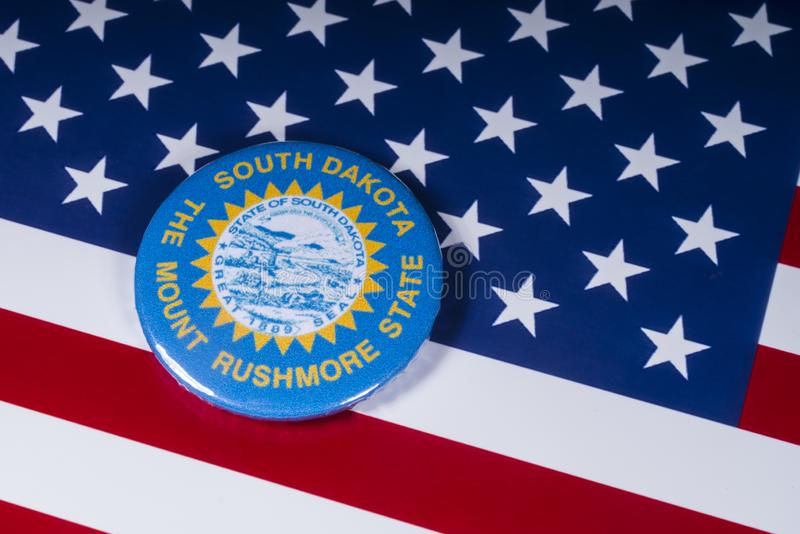 The State of South Dakota in the USA. London, UK - November 20th 2018: The symbol of the State of South Dakota, pictured over the flag of the United States of royalty free stock image