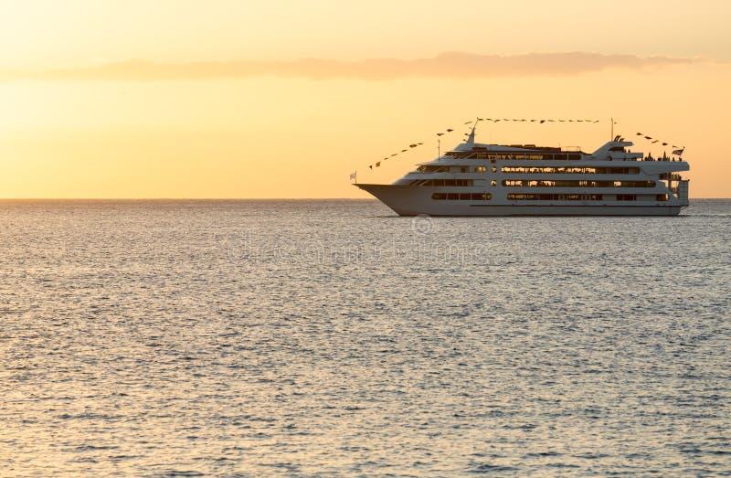 Statek wycieczkowy żegluje położenia słońce fotografia stock