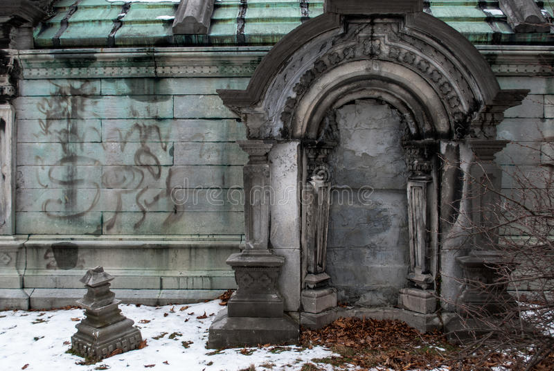 Stately Crypt. A stately crypt in an old cemetary in winter. The doorway is concreted over and it is severly deteriorated stock photo