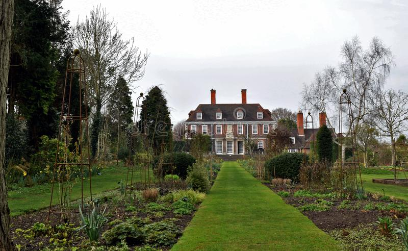 A stately home surrounded by a large garden. A grand Stately home in a Well maintained garden with well keep flower beds and near lawns royalty free stock photos