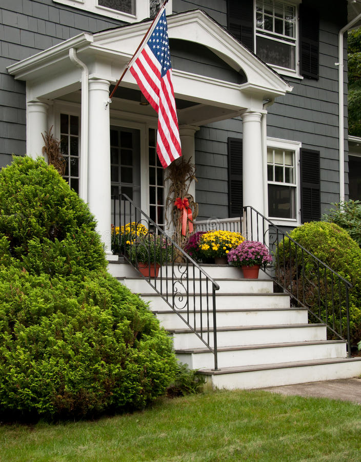 Stately house with flag overhanging steps. Stately grey house with colorful plants and flag overhanging steps stock photo